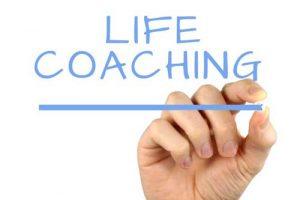 mano che scrive life coaching su lavagna trasparente