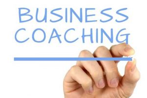 mano che scrive business coaching su lavagna trasparente